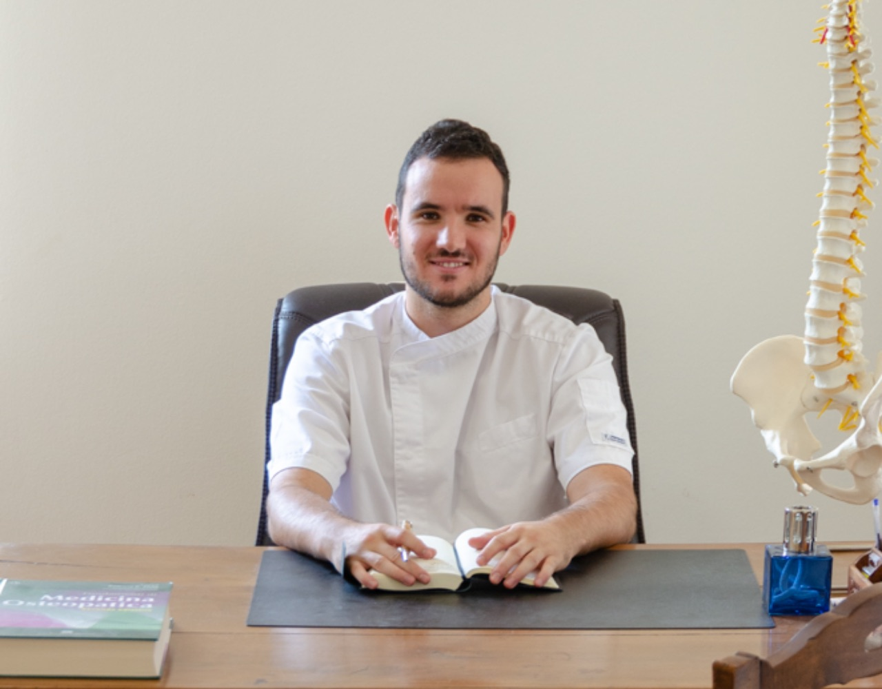 Osteopata Matteo Baggi seduto alla scrivania nel suo studio a Milano